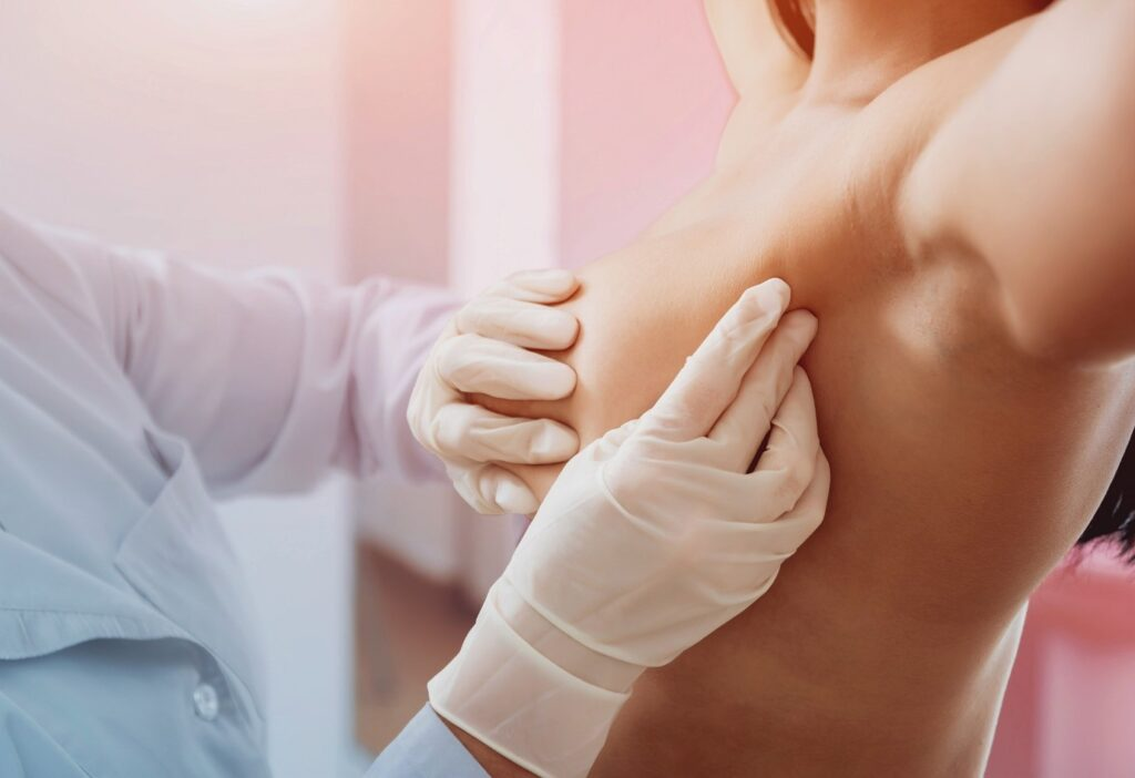 doctor checking breasts for signs of breast cancer