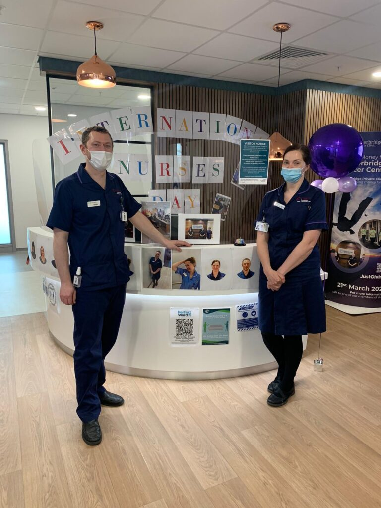 Colour photograph of two nurses from the Clatterbridge Private Clinic stood in front of the reception desk in the Liverpool clinic decorated with balloons, pictures and a banner for International Nurses Day 2021