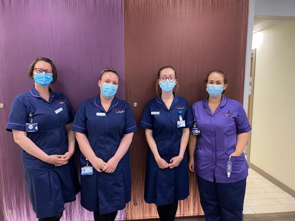 Colour photograph of left to right Laura Rowland, Senior Chemotherapy Nurse at Clatterbridge Private Clinic, Angela White, Chemotherapy Suite Manager at Clatterbridge Private Clinic, Amy Richardson, Chemotherapy Nurse at Clatterbridge Private Clinic and Clare Kelly, Chemotherapy Support Worker at the Clatterbridge Private Clinic stood against a purple wall in the clinic in uniform wearing facemasks