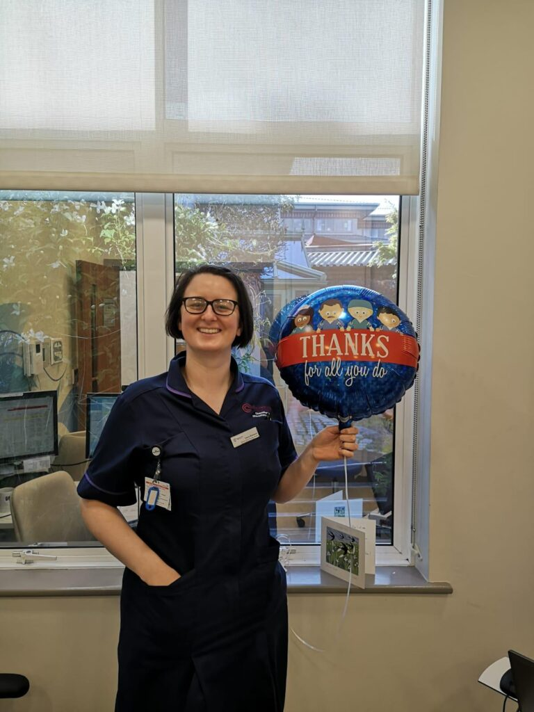 Colour photograph of Laura Rowland, Senior Chemotherapy nurse at the Clatterbridge Private Clinic holding a blue balloon with images of nurses and doctors on with the text thanks for all you do