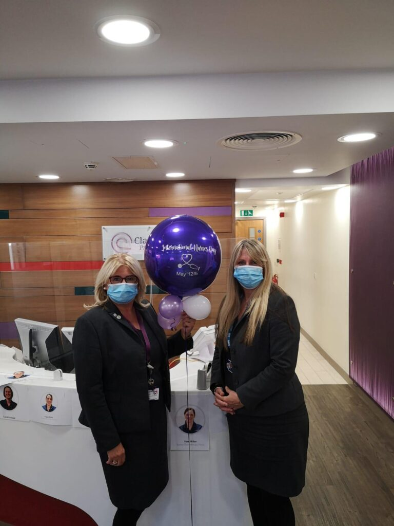 Colour photograph of Kim McBride, Receptionist at Clatterbridge Private Clinic and Gill Sloan, Patient Services Co-ordinator at the Clatterbridge Private Clinic, standing in reception with a purple balloon between them which says International Nurses Day May 12th