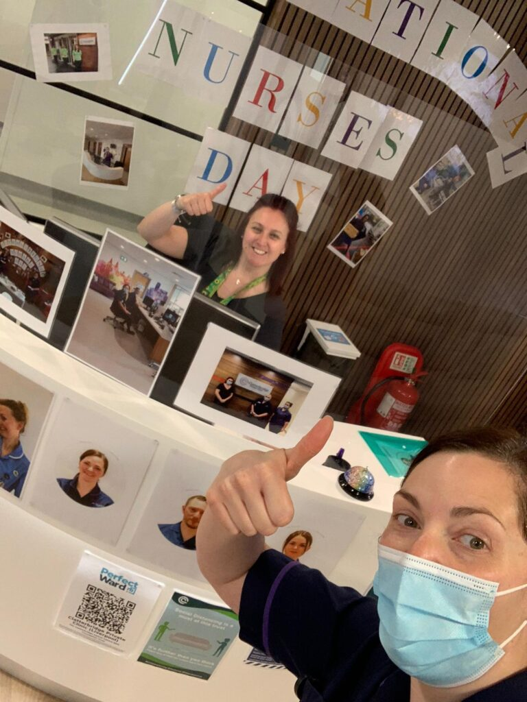 Colour photograph of two staff members at the Clatterbridge Private Clinic putting their thumbs up celebrating International Nurses Day 2021, one is sat behind the reception desk smiling, another is holding the camera taking the picture wearing a face mask